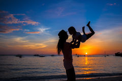 Little girl and her mother having fun at sunset on Stock Photo
