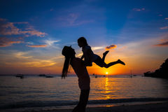 Little girl and her mother having fun at sunset on Stock Image