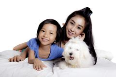 Little girl and her mother with their dog. Little girl and her mother lying on the bed with their cute dog, isolated on white background Stock Photo