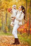 Little girl and her mother playing in the autumn park Royalty Free Stock Photo