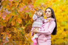 Little girl and her mother playing in the autumn park Stock Images