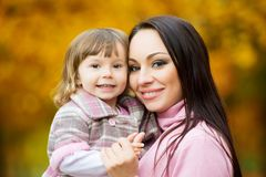 Little girl and her mother playing in the autumn park Stock Photography