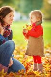 Mother and daughter in the park. Little girl and her mother playing in the autumn park Stock Photos