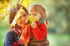 Mother and daughter in the park. Little girl and her mother playing in the autumn park Stock Image
