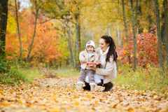 Little girl and her mother playing in the autumn park Royalty Free Stock Photography