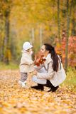 Little girl and her mother playing in the autumn park Royalty Free Stock Image