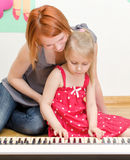 Girl and her mother playing the piano Royalty Free Stock Images