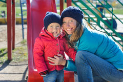 A little girl and her mother playing in a playground. Happy mother and daughter enjoying time together at playground Royalty Free Stock Image