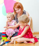 Little girl and her mother playing Stock Photos