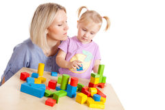 Little girl and her mother playing with toy blocks Royalty Free Stock Photos