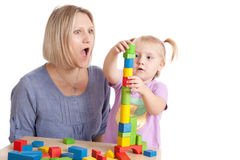 Little girl and her mother playing with toy blocks Stock Image