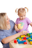 Little girl and her mother playing with toy blocks Royalty Free Stock Image