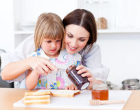 Little girl and her mother preparing toasts Royalty Free Stock Images