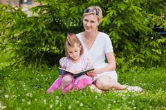Little girl and her mother reading a book Royalty Free Stock Photo