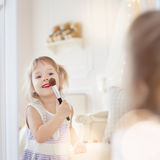 A little girl in her mother's room, using makeup to imitate adults.  Royalty Free Stock Images