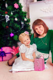 Little girl with her mother sitting at the Christmas Stock Image