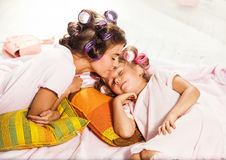 Little girl with her mother slipping in bed. Little girl slipping with her mother in bed on white Royalty Free Stock Image