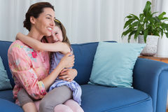 Little girl with her mother on sofa Royalty Free Stock Images