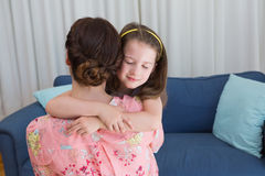 Little girl with her mother on sofa Stock Photo