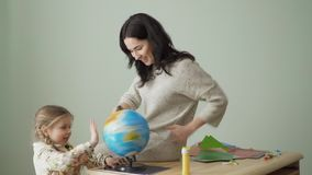 Young mother and little daughter spins the globe on table. Little girl and her mother are studying at home together. Family studies the geography and twists the stock footage