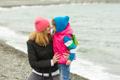 Little girl and her mother touching noses on beach in cold weather Stock Photo