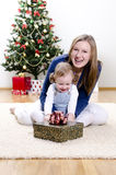 Little girl and her mother unpacks the gift Royalty Free Stock Photography