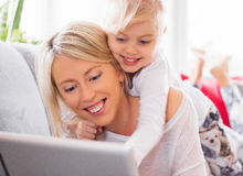 Little girl with her mother using tablet computer Stock Photo