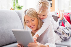 Little girl with her mother using tablet computer Royalty Free Stock Images