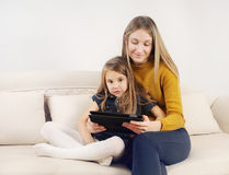 Little girl with her mother using tablet device on the sofa at h Stock Photo
