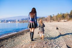 Little girl and her mother walking on the beach in Stock Photos