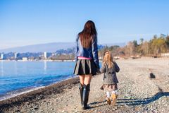 Little girl and her mother walking on the beach in Stock Photography