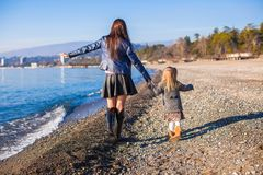 Little girl and her mother walking on the beach in Royalty Free Stock Image