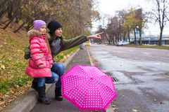 Little girl and her ??mother walking with umbrella Stock Photos