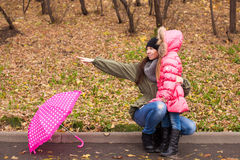 Little girl and her ??mother walking with umbrella Royalty Free Stock Images