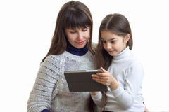 Little girl with her mother watching something on a mobile phone. Isolated on white background Stock Image