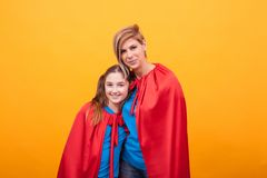 Little girl and her mother wearing superheros costume over yellow background.