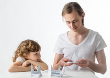 Little girl with her older brother does paper cranes Royalty Free Stock Images
