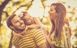 Little girl with her parents enjoy in nature. stock photos