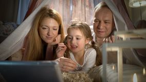 Little girl and her parents enjoying watching cartoons online in the tent in the nursery stock video footage