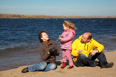 Little girl with her parents played on beach. Sunny autumn day Stock Images