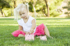 Little Girl with Her Piggy Banks Outside Stock Photography