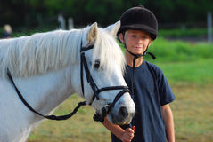 Little girl and her pony. A little girl child standing with her white cute pony on the paddock Stock Photography