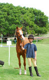 Little girl and her pony. A cute little preteen Caucasian girl with proud facial expression standing and holding her pony before horse riding training Royalty Free Stock Image