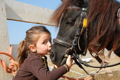 Little girl and her pony. Little girl kissing and her purebred shetland pony Stock Image