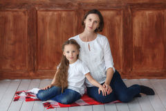 Little girl and her pregnant mom sitting in studio stock image