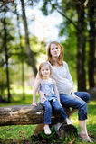 Little girl and her pregnant mother. Outdoors Stock Images