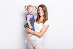 Little girl with her pregnant mother in studio. A little girl with her pregnant mother in studio Royalty Free Stock Photos