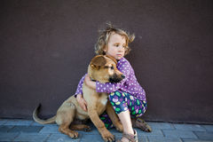 Little girl with her puppy. Little girl giving hugs to her puppy, looking in the same direction, wind in her hair Royalty Free Stock Photography