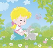 Little girl and her small rabbit. Smiling child playing with a grey bunny among flowers on green grass on a summer day, vector illustration in a cartoon style stock illustration