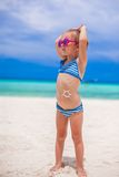 Little girl on her stomach painted a smile by sun Stock Photo